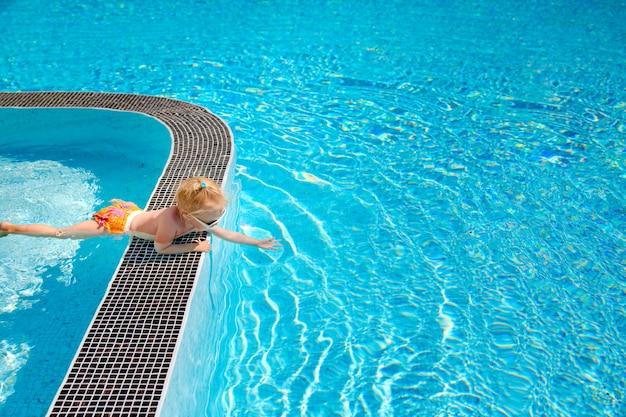 La pequeña niña rubia linda, acostada al lado de la piscina