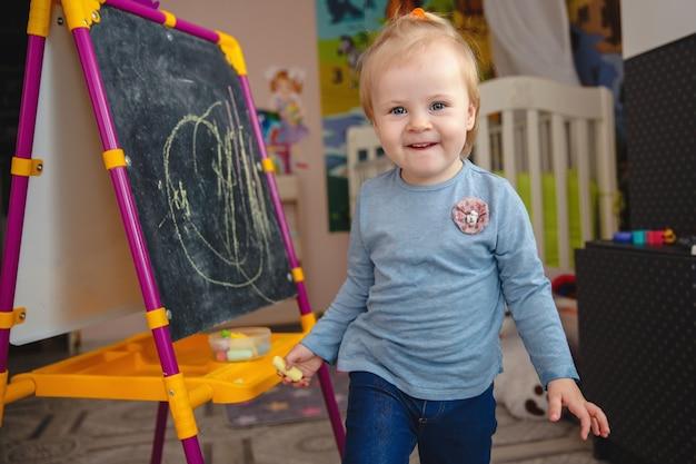 Una pequeña niña rubia sonriente en su casa en la sala de juegos cerca de la pizarra con tiza en sus manos. foto de alta calidad