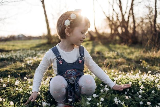 La pequeña niña sentada cerca de las flores