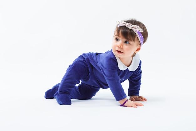 Pequeña niña sonriente adorable linda con el arco en el pelo arrastrándose