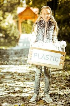 Una pequeña niña sonriente sosteniendo una caja de plástico en un buen día.