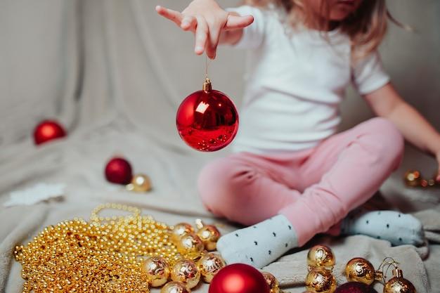 La pequeña niña sostiene bolas rojas de navidad.