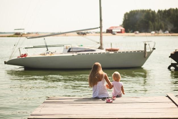 Una pequeña niña y su madre están sentadas en el muelle en un soleado día de verano. son rubios y vestidos con vestidos blancos, mirando el yate blanco.