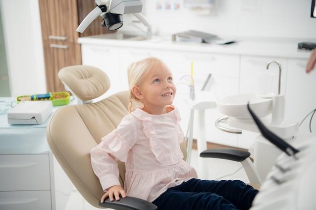 Una pequeña paciente dentista satisfecha mostrando su sonrisa perfecta después del tratamiento dental en una clínica