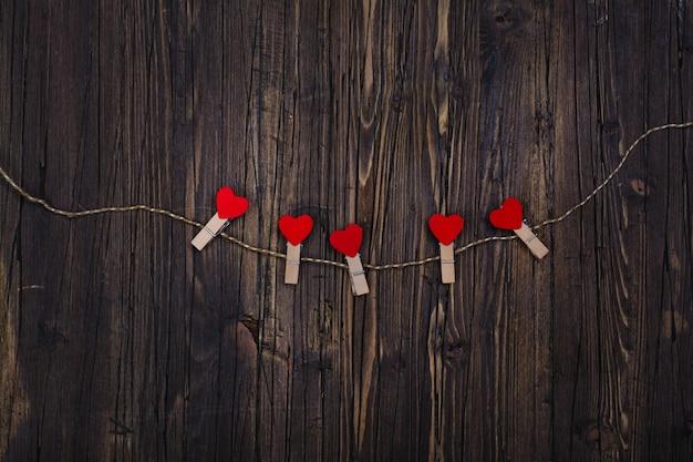 Pequeña pinza de madera con corazones rojos colgando de una cuerda