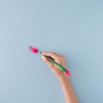 Una pequeña pluma y la mano que sostiene la pluma sobre fondo azul pastel. colocación plana mínima.