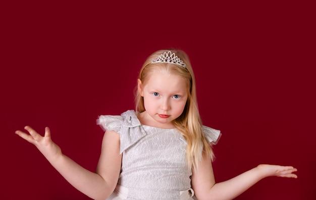 Pequeña princesa rubia hermosa que baila en el vestido blanco y de plata de lujo aislado en fondo rojo. cara divertida, diferentes emociones