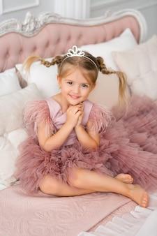 Pequeña princesa en un vestido de noche está acostada en una hermosa cama