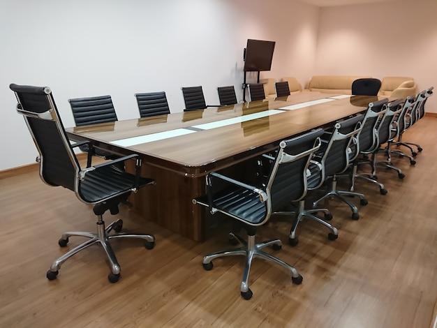 Pequeña sala de reuniones con asientos de cuero negro.