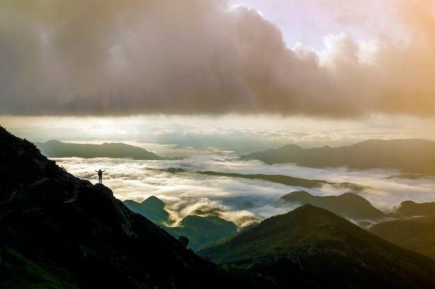 Pequeña silueta de turista con mochila en la ladera de la montaña rocosa