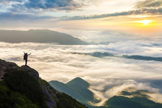 Pequeña silueta de turista con mochila en montaña rocosa