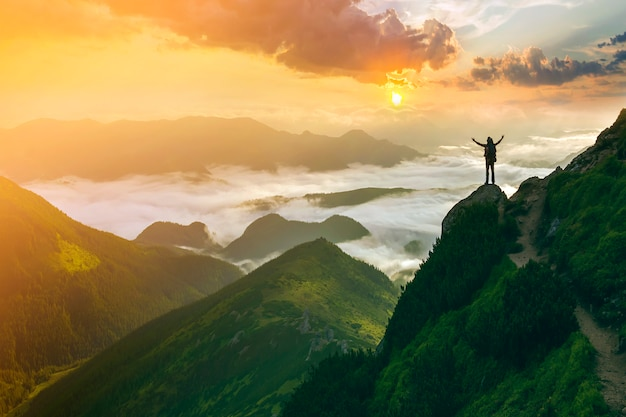 Pequeña silueta de turista en montaña rocosa con las manos levantadas