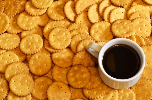 Pequeña taza de café y galleta salada.