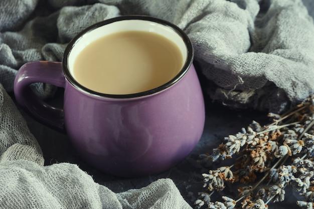 Una pequeña taza morada con una bebida caliente.