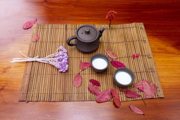 Una pequeña tetera de arcilla con dos tazas para bebidas de pie sobre una estera entre hojas rojas de árboles y una ramita de lavanda
