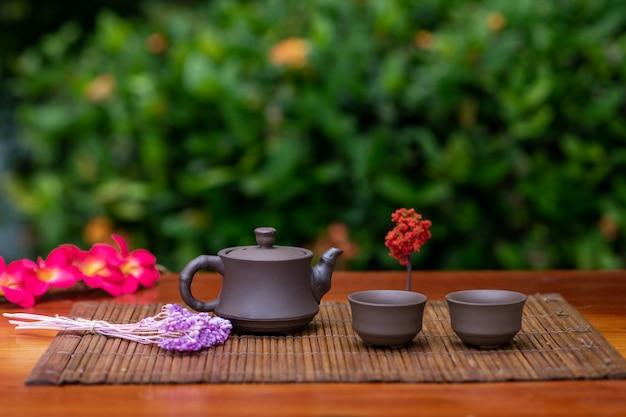 Una pequeña tetera de arcilla con dos tazas para bebidas de pie sobre una estera rodeada de ramas con flores.
