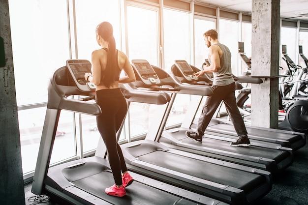 Una pequeña vista de la gran sala de deporte donde dos personas hacen ejercicio. están funcionando en máquinas elípticas. el ejercicio es intensivo y duro.