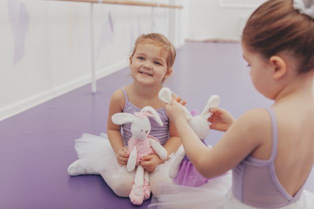 Pequeñas bailarinas adorables descansando después de hacer ejercicio y bailar, copie el espacio