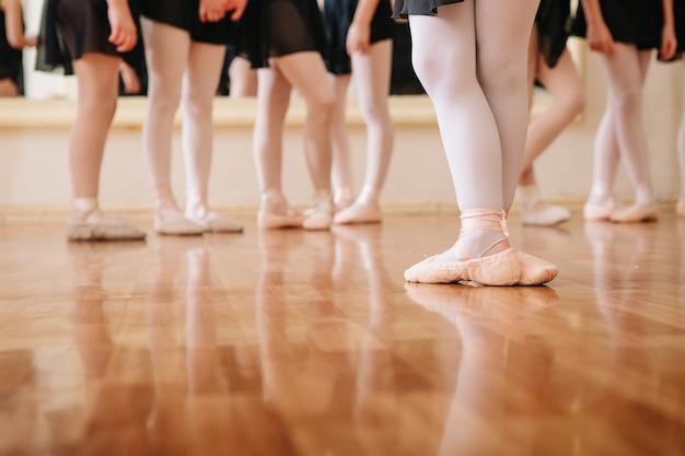 Pequeñas bailarinas que hacen ejercicios clase de ballet.