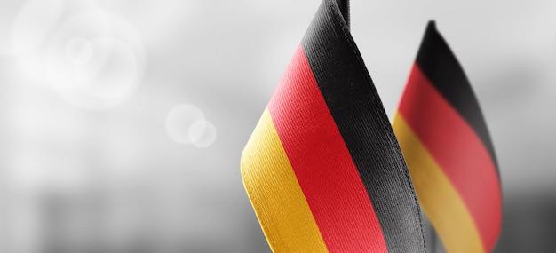Pequeñas banderas nacionales de alemania en una pared borrosa de luz