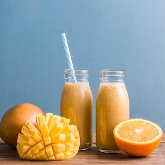 Pequeñas botellas de batido con mango y naranja