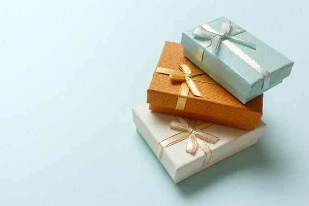 Pequeñas cajas de regalo se apilan sobre un fondo turquesa pastel. regalos de navidad.