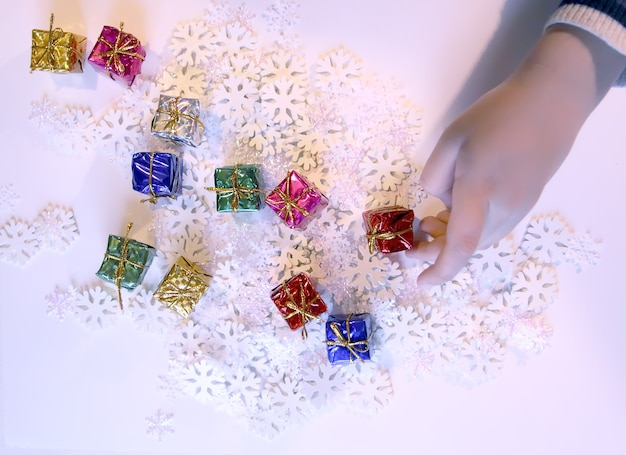 Pequeñas cajas de regalo de colores en las manos del niño. proceso de decoración navideña y año nuevo.