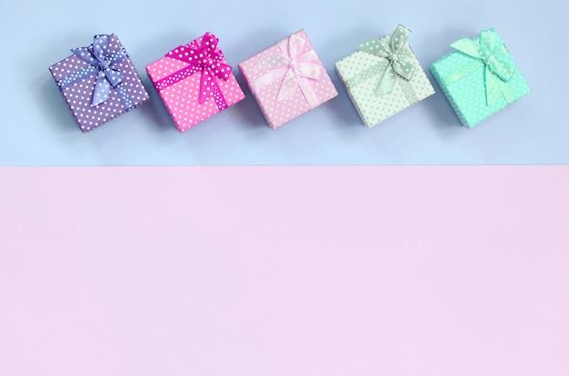 Pequeñas cajas de regalo de diferentes colores con cintas se encuentran sobre un fondo violeta y rosa