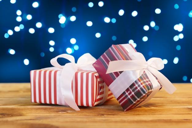 Pequeñas cajas de regalo de navidad en mesa de madera contra luces bokeh