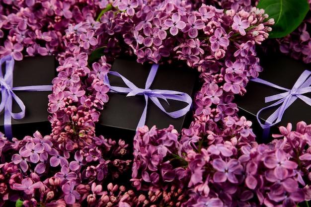 Pequeñas cajas de regalo negras envueltas en cinta morada con lila natural.