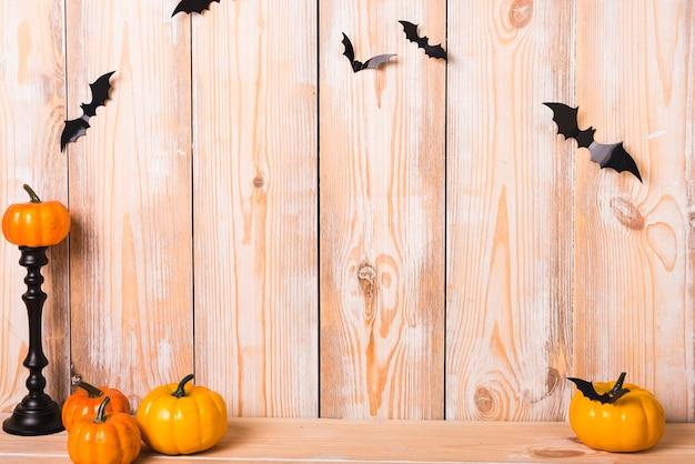 Pequeñas calabazas y murciélagos cerca de la pared