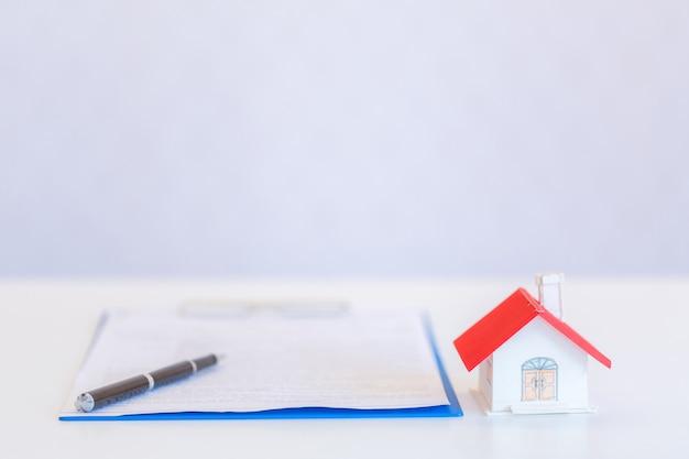 Pequeñas casas de diseño moderno y documentos con bolígrafo sobre blanco.