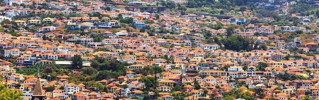 Pequeñas casas de ladrillo con techo naranja en las colinas, portugal, madeira