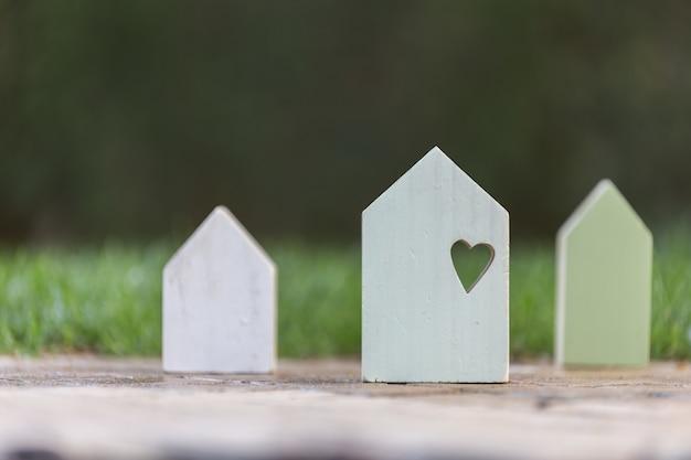 Pequeñas casas de madera con un corazón en el grande que simboliza el amor familiar y la seguridad en el hogar.