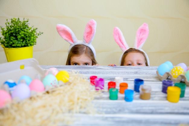Pequeñas chicas curiosas con orejas de conejo que se asoman desde detrás de la mesa de la cocina con sabrosos huevos de pascua y mirando con sorpresa.