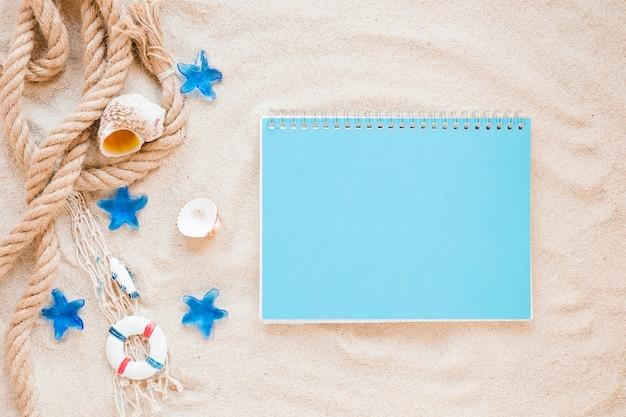 Pequeñas conchas marinas con cuerda náutica y cuaderno.