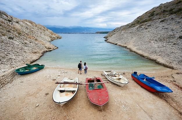 Pequeñas embarcaciones a motor en la acogedora costa portuaria entre altas costas rocosas y dos jóvenes turistas, hombre y mujer con mochilas tomados de la mano de pie al borde del agua