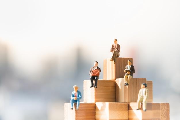 Las pequeñas figuras de los hombres de negocios que se sientan en bloques de madera caminan con fondos de la ciudad.