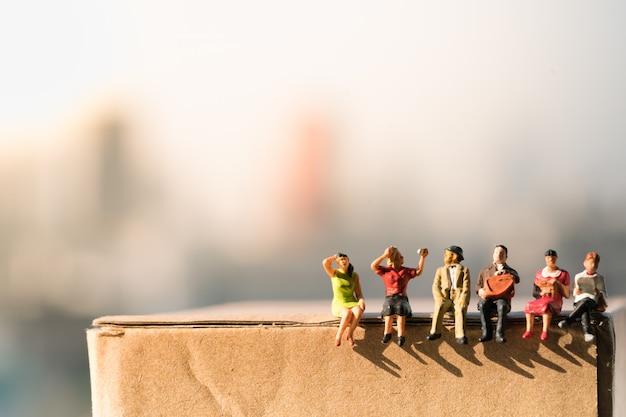 Pequeñas figuras sentadas en caja de papel con fondos de la ciudad.