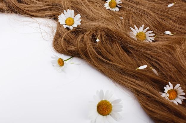 Pequeñas flores blancas se encuentran en los rizos de cabello castaño