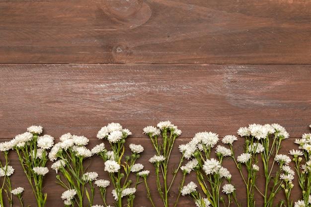 Pequeñas flores blancas sobre fondo de madera.