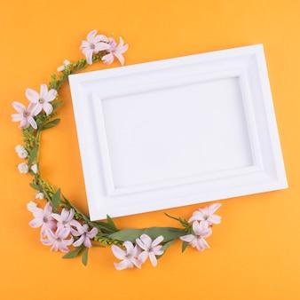 Pequeñas flores con hojas verdes y marco en blanco.