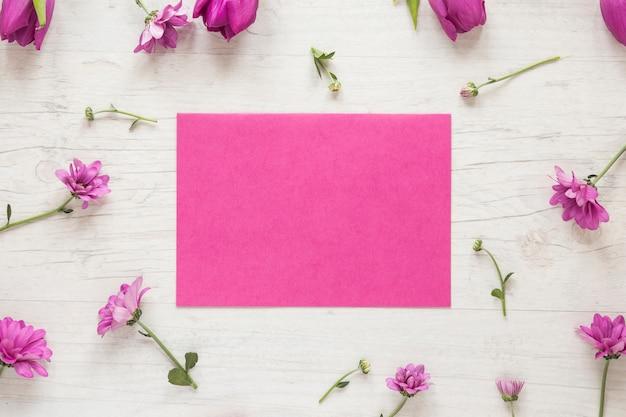 Pequeñas flores moradas con papel sobre mesa.