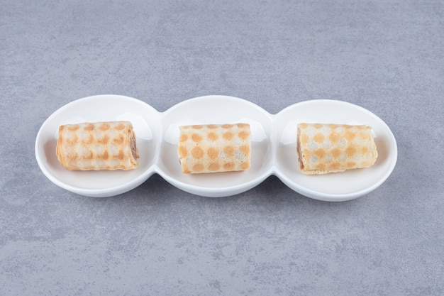 Pequeñas galletas en un plato para servir rodeadas de palitos de canela sobre mármol