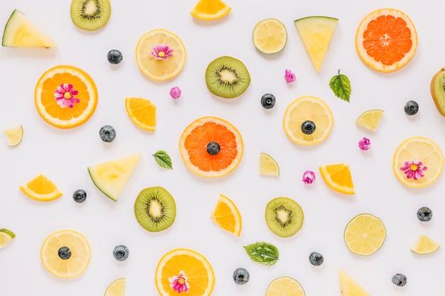 Pequeñas hojas y flores cerca de rebanadas de frutas