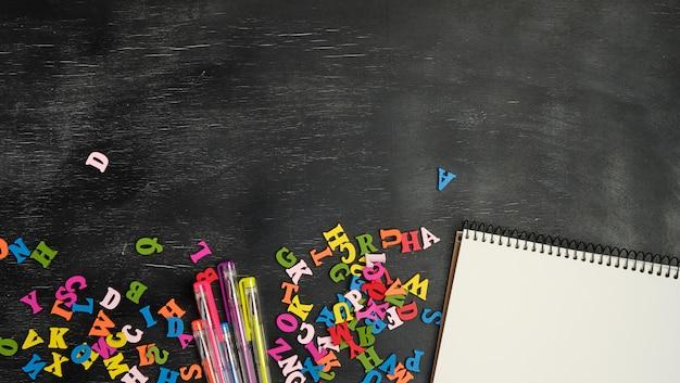 Pequeñas letras de madera multicolores del alfabeto inglés y cuaderno de papel