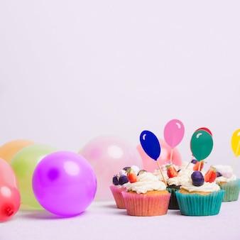 Pequeñas magdalenas con globos en mesa blanca