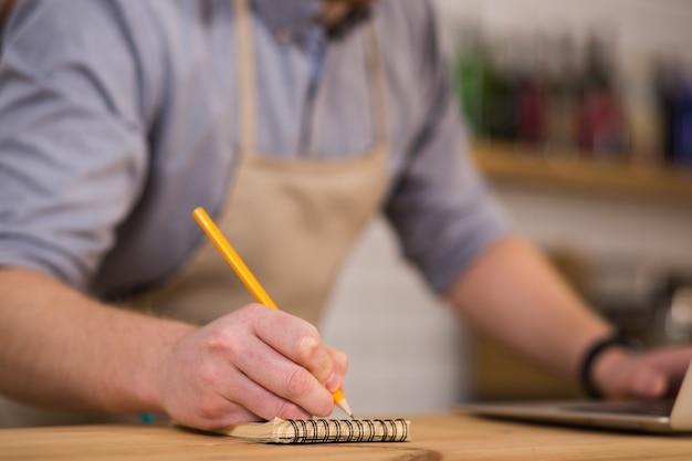 Pequeñas notas. enfoque selectivo de un lápiz utilizado por un hombre agradable y agradable para tomar notas mientras trabaja en la cafetería.