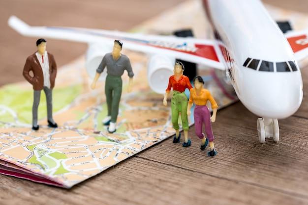 Pequeñas personas de juguete están en el mapa frente al avión.
