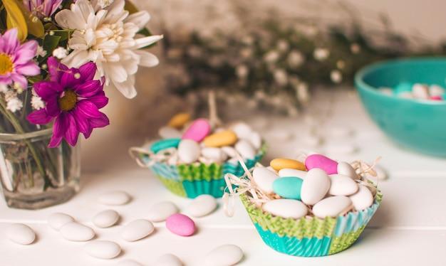 Pequeñas piedras brillantes en canastas cerca de jarrón con ramo de flores